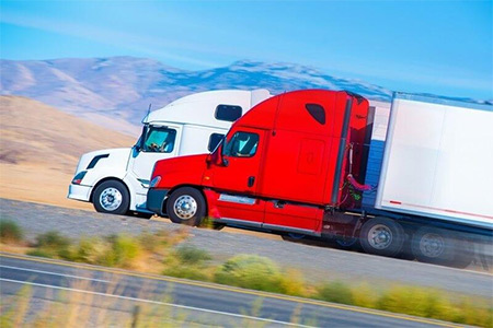 Two trucks on a road - Long distance movers Las Vegas